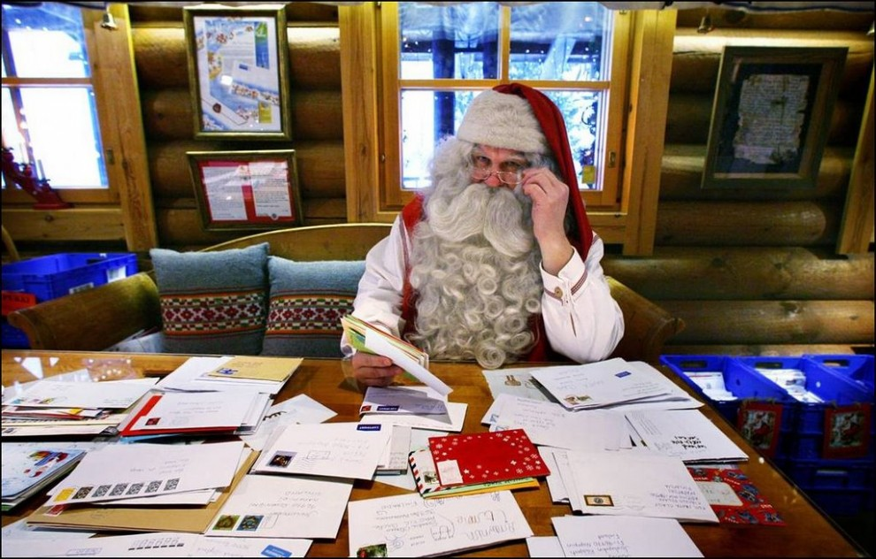 10) Санта Клаус читает письма детей со всего мира за Полярным кругом, возле финского города Рованиеми. (Bob Strong/Reuters)