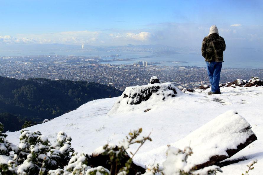 15. Карлос Беласко из Ливерпуля стоит на покрытой снегом горе Grizzly Peak и наслаждается видом, открывающимся отсюда на залив, Сан-Франциско и Восточный залив. Холодная арктическая метель накрыла холмы Окланд-Беркли несколькими сантиметрами снега в Беркли, Калифорния. (AP Photo/Dino Vournas)