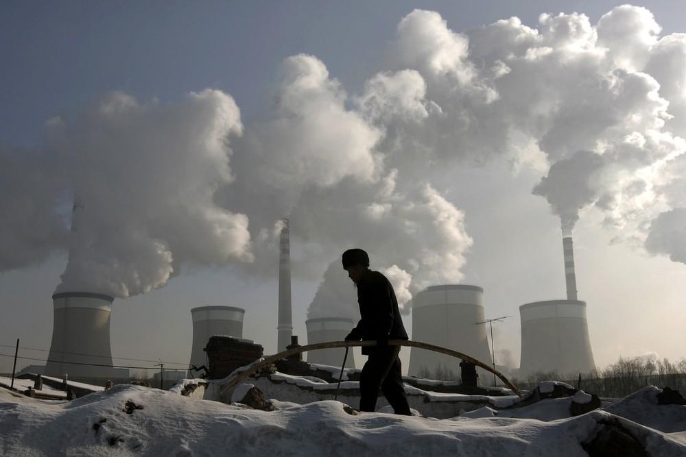 15) Житель деревни идет мимо электростанции, работающей на угле на окраине Датонга, провинция Шаньси, 20 ноября 2009 года. Китай поднял цены на электричество для не городских жителей примерно на 5,4%. Это был первый подъем с июля 2008 года, необходимый в качестве компенсации фирмам, понесшим потери из-за государственных расходов на цены. (REUTERS/Jason Lee)
