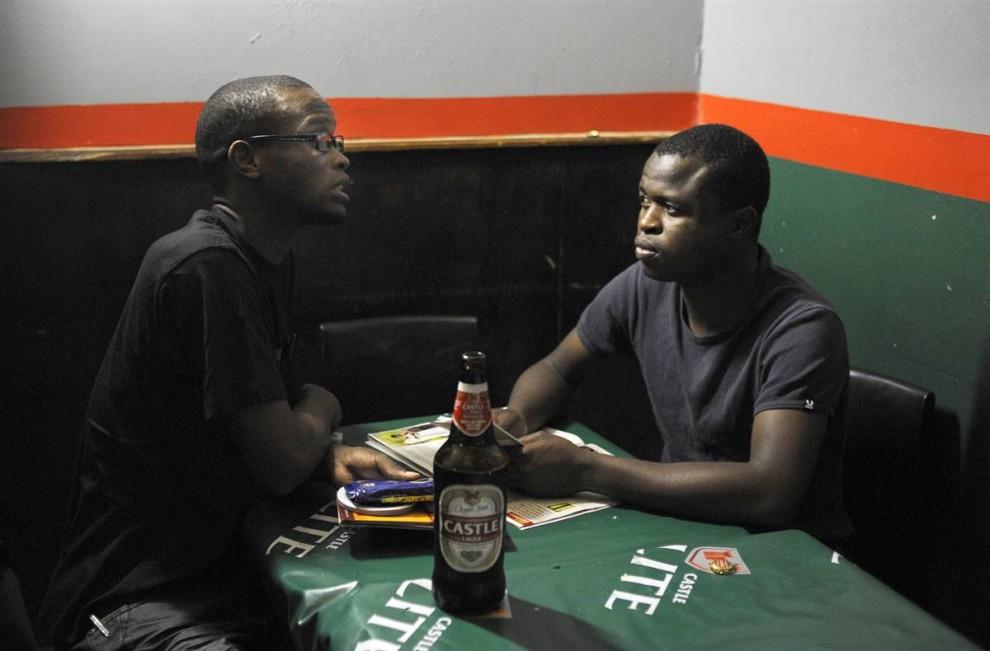 16. Работник организации медицинских исследований раздает презервативы и брошюры во время разговора с человеком в баре недалеко от Йоханнесбурга, Южная Африка, чтобы донести до него всю важность безопасного секса и предотвратить распространение СПИДа. Образ сильно пьющего бесстрашного соблазнителя до сих пор привлекает многих жителей Южной Африки, порождая главную проблему остановить СПИД в стране, где из 48 миллионов человек 5,7 миллионов инфицированных. (Stephane de Sakutin / AFP - Getty Images)