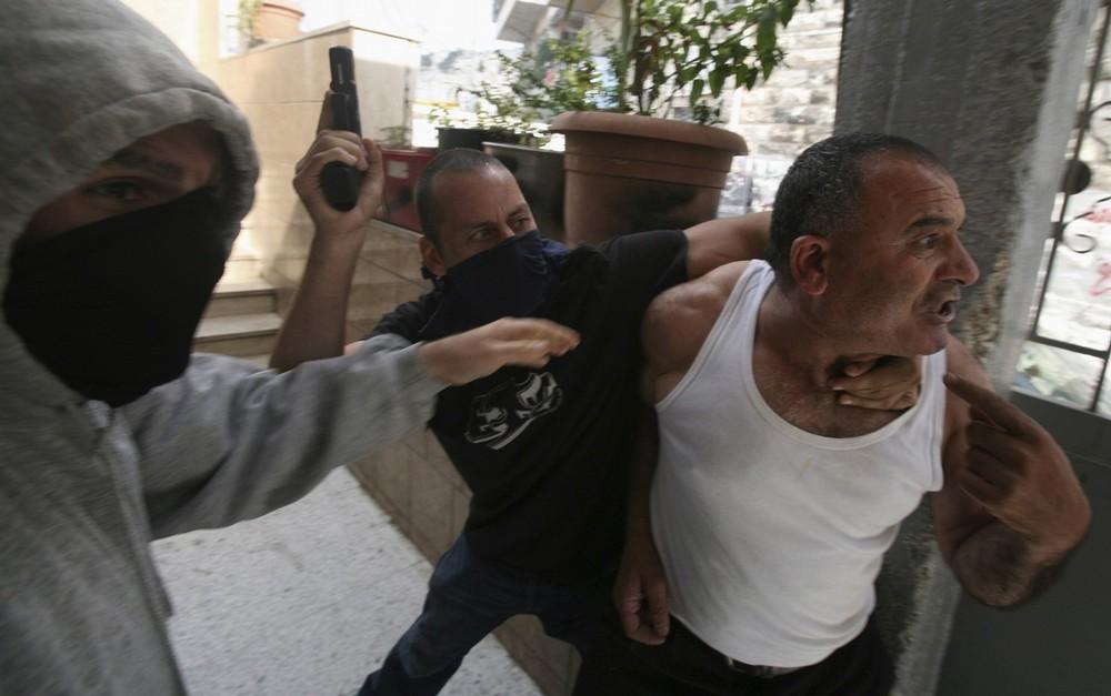 16. Офицеры израильской полиции под прикрытием дерутся с палестинцем, сына которого задержали во время протестов в районе Восточного Иерусалима Рас ал-Амуд 9 октября 2009 года. В четверг палестинские лидеры сообщили о всеобщей забастовке и предупредили о дальнейших протестах в мусульманский день пятничных молитв в мечети ал-Акса. Израиль сообщил, что не воспринимает предупреждения Палестины о всеобщем восстании всерьез. (REUTERS/Baz Ratner)