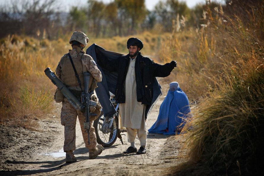 16. Морпех США из второго батальона обыскивает афганца во время операции по поиску боевиков после перестрелки в округе Гармсир в провинции Гильменд, южный Афганистан. (AP Photo/Kevin Frayer)