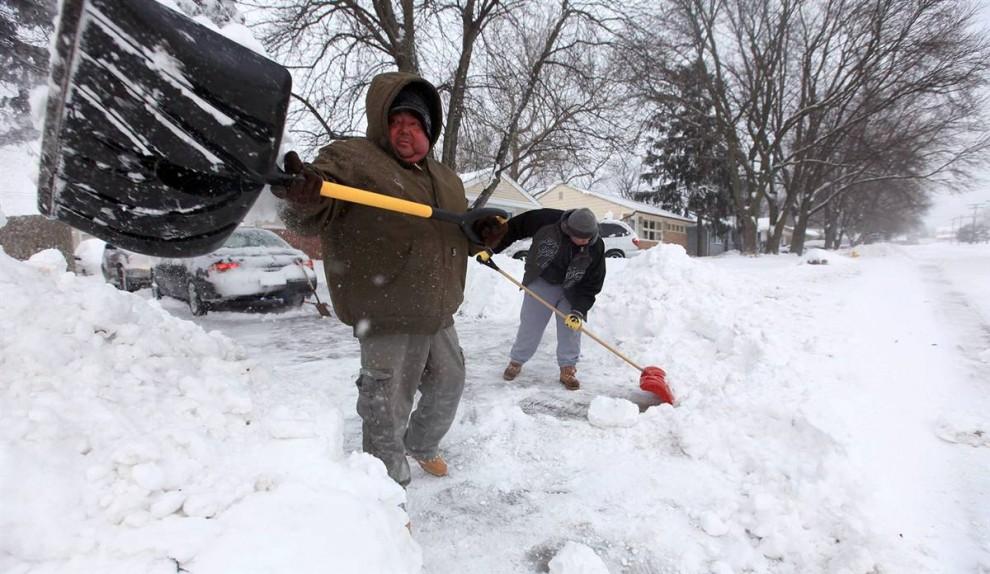 13. Марлон Кабрера (слева) и Питер Паломек разгребают снег с проезда на улице 19th St. В Де-Мойне, Айова, утром в среду 9 декабря. (Rodney White / The Des Moines Register)