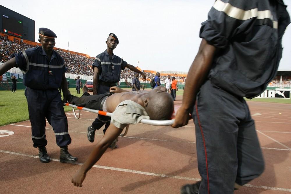 17. Пожарные уносят со стадиона молодого человека, пострадавшего во время отборочного матча на Чемпионат мира по футболу 2010 между сборными Кот-д'Ивуара и Малави в Абиджане 29 марта 2009 года. По меньшей мере 19 человек погибли в воскресенье, когда напора желавших посмотреть матч не выдержала стена стадиона. Тогда полиция использовала слезоточивый газ, чтобы расчистить место, что вызвало давку, в которой серьезно пострадали многие зрители. (REUTERS/Luc Gnago)