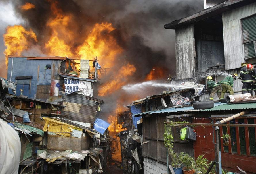 17. Пожарные сражаются с огнем с крыши другого дома в пригороде Пасай Сити на юге Манилы, Филиппины. Сильный пожар разгорелся в районе хижин, сделанных, в основном, из легковоспламеняющихся материалов. (AP Photo/Pat Roque)