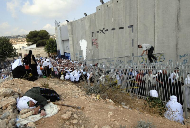 16) Пожилая палестинка спит у израильской разделительной стены, пока тысячи ее соотечественников ждут разрешения на пересечение военного контрольного пункта в Иерусалим из Вифлеема 5 октября 2007 года. Израильское правительство разрешило только мужчинам за 50 и женщинам за 40 входить в Иерусалим для молитвы в мечети Ал Акса – третьем священным месте религии ислам. (UPI Photo/Debbie Hill)