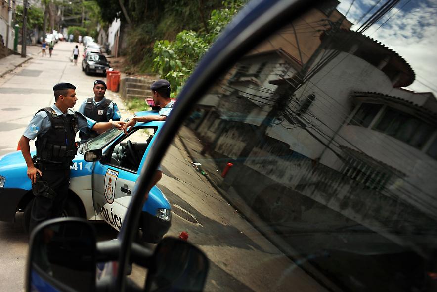 18. Полицейские патрулируют район трущоб Вавилония 3 декабря 2009 года в Рио-де-Жанейро. Эвакуаторы только что освободили дорогу для полицейских машин. (Photo by Spencer Platt/Getty Images)