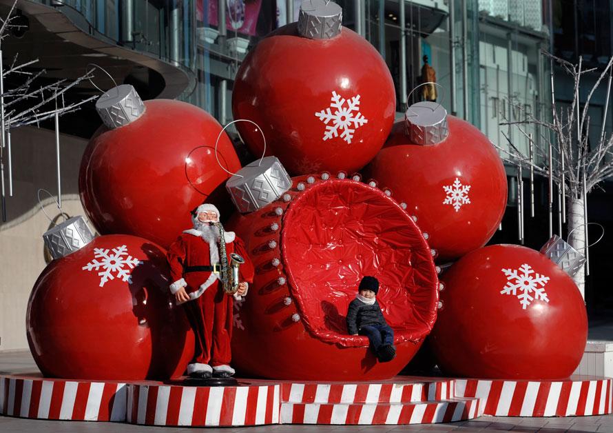 18) Ребенок сидит на огромной елочной игрушке у торгового центра в Пекине. (AP Photo/ Andy Wong)