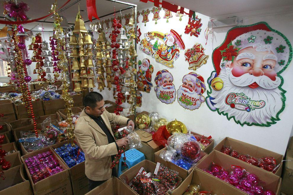 18) Покупатель рассматривает новогодние игрушки. Китай является крупным экспортером новогодних украшений. (EPA / 26 ноября 2009/ Китай)