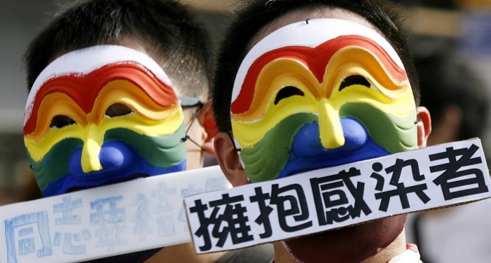 19. Участники тайваньского гей-парада в масках в Тайбэе. Примерно 25 000 тайваньцев собрались с людьми из других стран, включая Малайзию, Корею и Японию, на седьмой ежегодный гей-парад. На табличках написано на китайском: «Обнимите ВИЧ-инфицированных» и «Геи хотят жениться». (Pichi Chuang / Reuters)