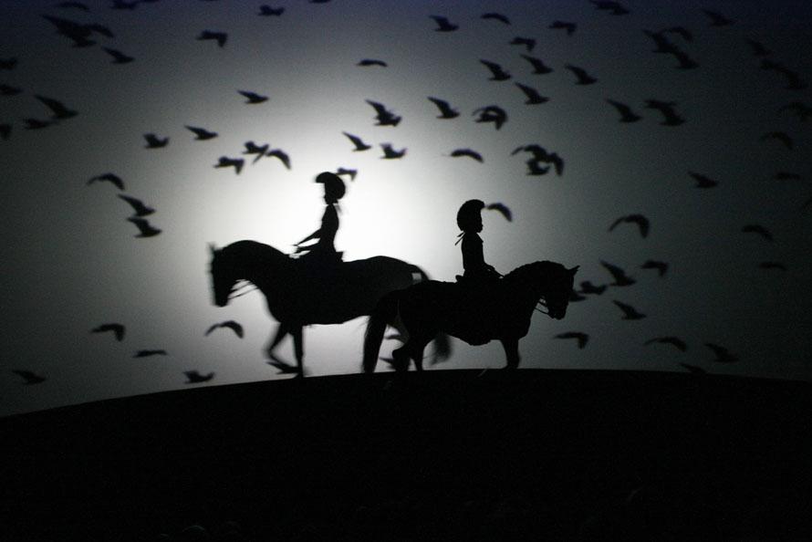 19. Силуэты лошадей и их наездников на фоне подсвечивающегося экрана во время «Даршана» - инновационного шоу от французского мастера верховой езды Бартабаса. «Даршан», во время которого лошади находятся на внешней стороне арены, а зрители – внутри, дебютировало в театре Бартабаса в пригороде Парижа Форт-д'Обервилье. (AP Photo/Francois Mori)