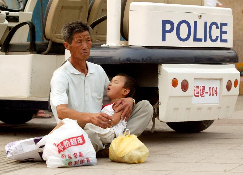 18) Китаец держит на руках своего спящего сына у полицейского участка, пока его семья ждет такси на одной из ж/д станций Пекина 26 июля 2008 года. Из-за серьезных транспортных ограничений в преддверии Олимпийских игр жители и туристы были вынуждены простаивать длинные очереди на автобусы, метро и такси. (UPI Photo/Stephen Shaver)