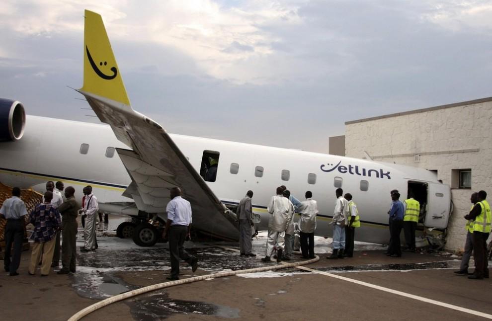 19. Представители властей Руанды смотрят на самолет компании «Jetlink», врезавшийся в зону VIP в аэропорту Кигали 12 ноября 2009 года. Пассажирский самолет, направлявшийся в Уганду, врезался в VIP-зону в столице Руанды. В результате погиб один пассажир. (REUTERS/Hereward Holland)