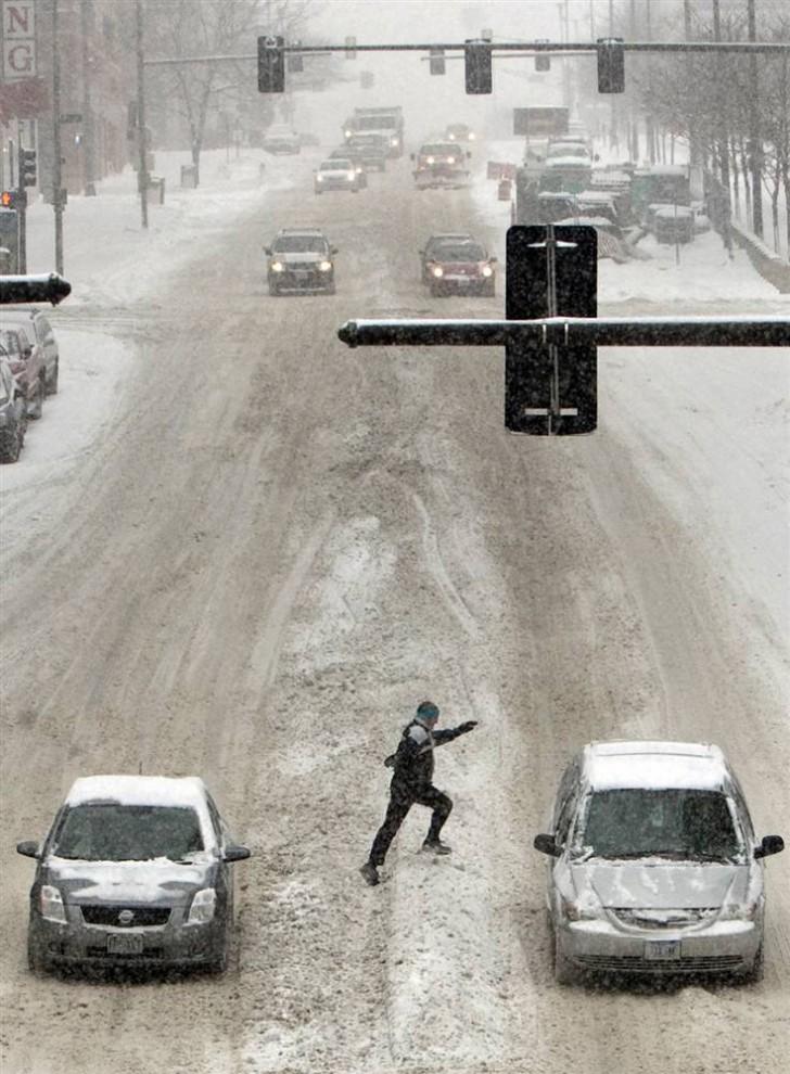 16. Пешеход перепрыгивает через сугроб снега, пересекая улицу, в центре Омахи, штат Небраска. (Nati Harnik / AP)