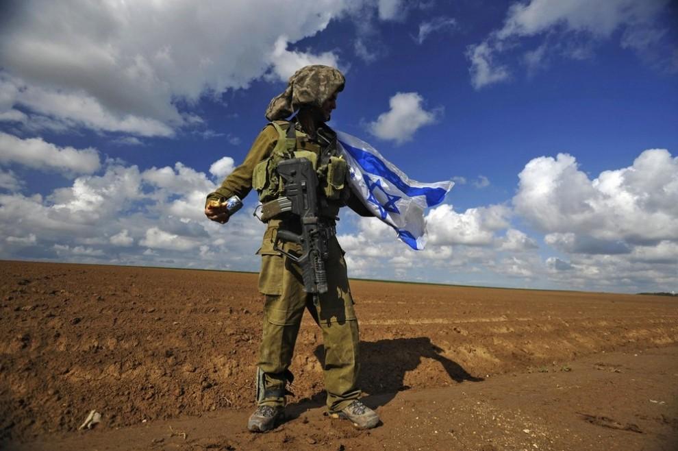 20. Израильский солдат держит национальный флаг, пересекая границу обратно в Израиль из Сектора Газа 18 января 2009 года. Исламской движение сопротивления «Хамас» сообщило, что прекратит огонь одновременно с другими группами боевиков в Секторе Газа и даст Израилю, который уже объявил перемирие со своей стороны, неделю на вывод своих войск с их территории. (REUTERS/Amir Cohen)