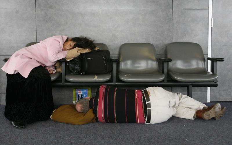 20) Уставшие путешественники спят в зале Международного аэропорта О'Хэйр в Чикаго 1 декабря 2006 года. Первые метели того года дошли до северного Иллинойса, Висконсина и Мичигана, став причиной задержки и отмены рейсов в аэропорту Чикаго. (UPI Photo/Brian Kersey)