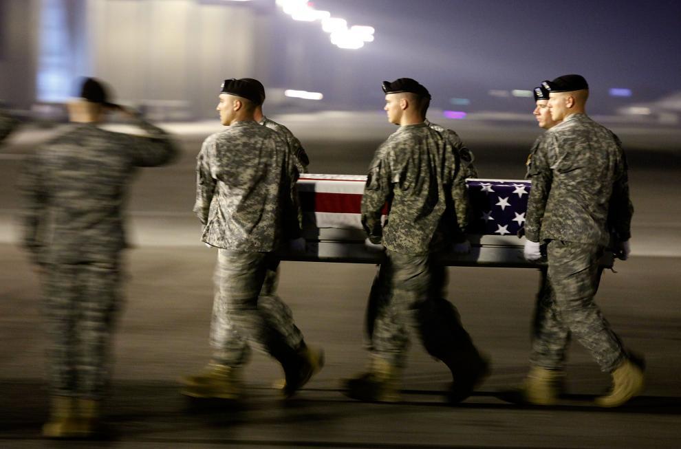 21) Члены американской армии несут гроб с телом сержанта Аарона М. Смита, который погиб в Афганистане. (Mark Wilson/Getty Images News/ fotobank.ua / 3 октября 2009/ США)