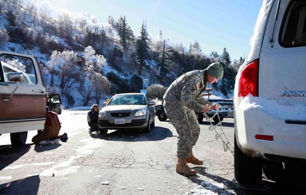 18. Томас Далтон (справа) из Оушенсайда, Нью-Йорк, снимает с автомобиля цепь противоскольжения недалеко от Биг Бэр Лэйк, штат Калифорния. (Jae C. Hong / AP)