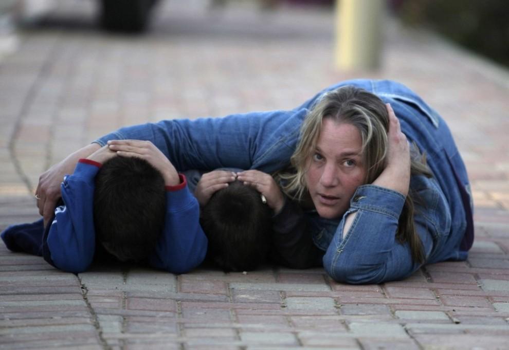 22. Израильская женщина и ее дети укрываются во время бомбардировки недалеко от Кфар Аза на севере Сектора Газа 7 января 2009 года. Женщина приехала навестить мужа – израильского офицера, ныне служащего на границе Газа. Бомбы взорвались, когда они ждали его. В среду Израиль отложил решение вопроса о том, чтобы послать свои вооруженные войска для штурма городских центров Сектора Газа. Об этом сообщил официальный представитель правительства Израиля, ссылаясь на египетские и французские усилия защитить перемирие с организацией «Хамас». (REUTERS/Baz Ratner)