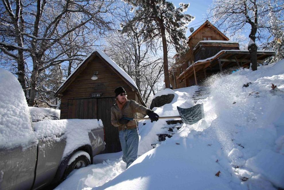 19. Джозеф Моспан разгребает снег перед своим домом в Арроубэр Лэйк, Калифорния. (Jae C. Hong / AP)