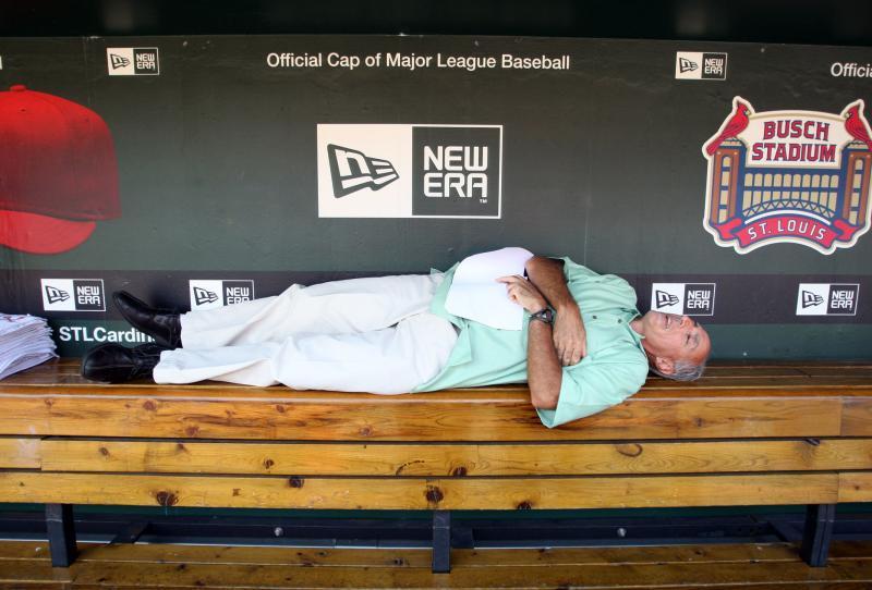 21) Работник службы громкоговорящих оповещений на стадионе Буш Джон Улет спит на скамейке запасных команды «St. Louis Cardinals» перед матчем против «Houston Astros» 27 августа 2009 года. (UPI/Bill Greenblatt)