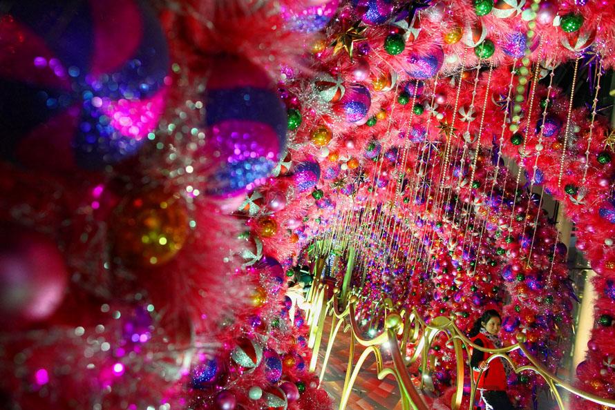 22. Китаец идет мимо рождественской елки, установленной перед офисным зданием в Пекине. С каждым годом Рождество становится все более популярным среди жителей Китая и постепенно проникает в китайскую культуру. (Photo by Feng Li/Getty Images)
