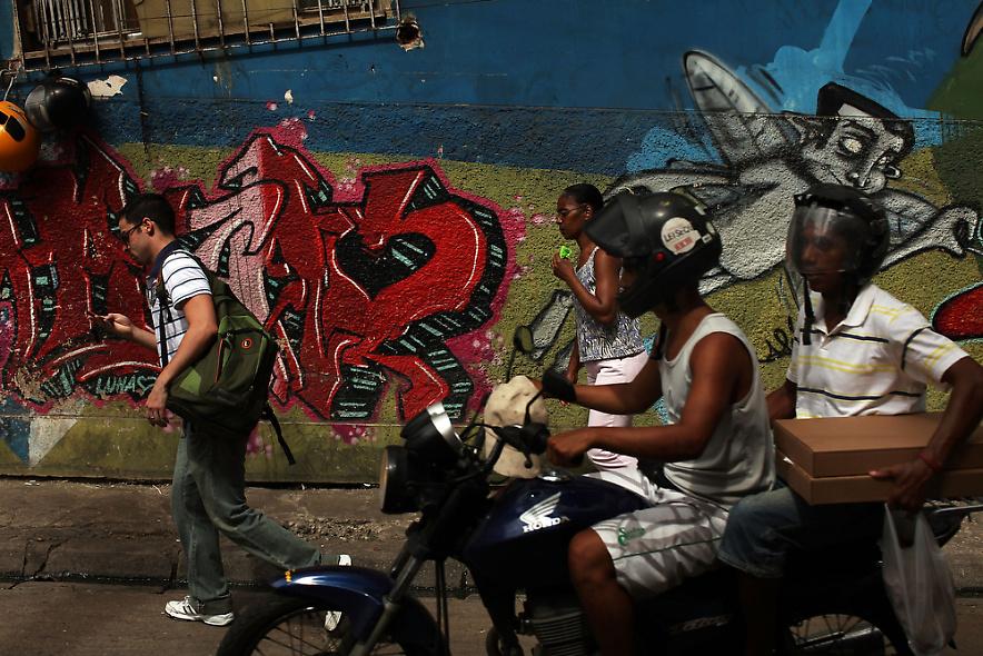 24. Люди на фоне стены с граффити в недавно «зачищенном» районе фавел Вавилония 3 декабря 2009 года в Рио-де-Жанейро. (Photo by Spencer Platt/Getty Images)