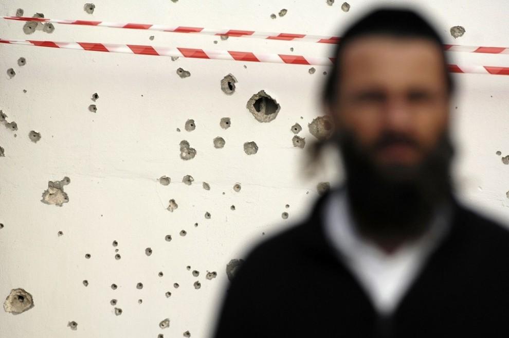 24. Ультра-ортодоксальный еврей стоит рядом с местом обстрела палестинскими боевиками в Газе в портовом городе Ашдод 16 января 2009 года. Израиль сообщил, что в пятницу их атаки на Сектор Газа могут вступить в «последнюю стадию», и выслал представителя для переговоров о перемирии после того, как организация «Хамас» прекратила огонь и вместе с ним трехнедельный конфликт, в котором погибло более 1100 палестинцев. (REUTERS/Amir Cohen)