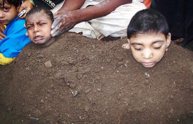 24) Детей частично похоронили в куче навоза в Гульбарга, Индия, надеяь на их исцеление во время полного солнечного затмения. (EXCEL MEDIA / REX FEATURES)