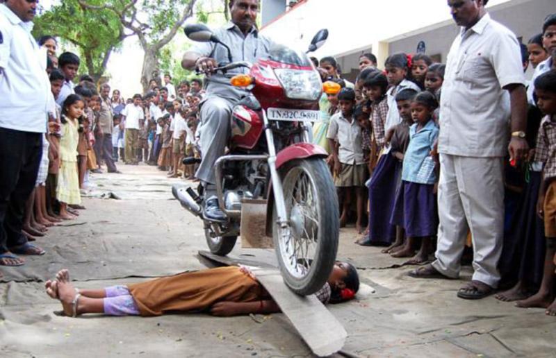 """23) Мотоциклист едет на доске, поставленной на школьницу во время """"показа мужества"""", организованного правительством начальной школы в Виллупурам (Villupuram) в индийском штате Тамил Наду… (AFP/GETTY)"""