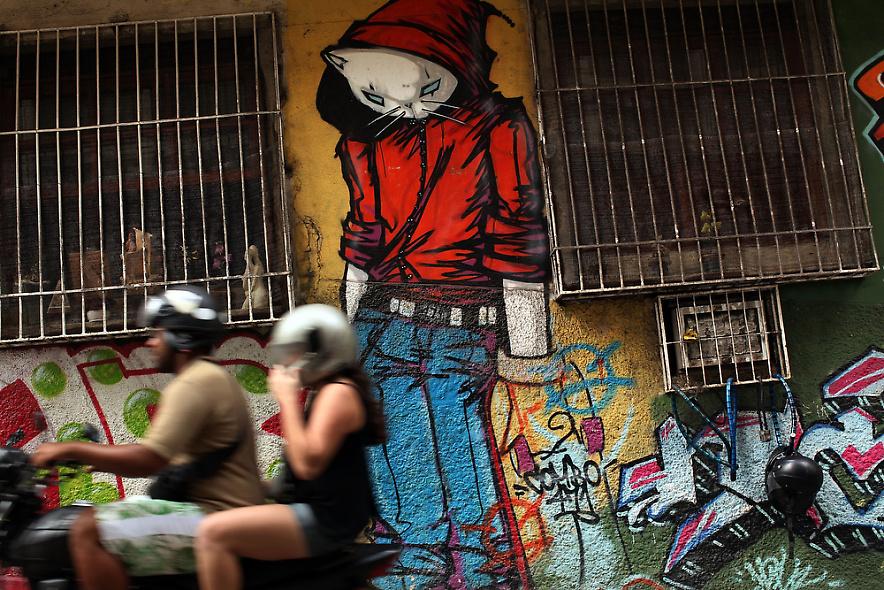26. Люди проезжают мимо стены с граффити в недавно «зачищенном» районе Рио-де-Жанейро 3 декабря 2009 года. (Photo by Spencer Platt/Getty Images)