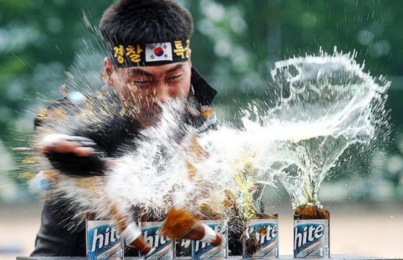 24) Полицейский из сеульского агентства полиции специальной оперативной группы разбивает ударом пивные бутылки во время демонстрации боевых навыков. (REUTERS)