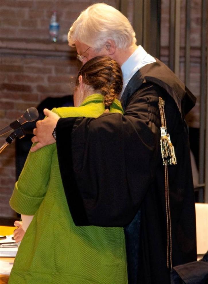 26. Нокс обнимает своего адвоката Лучиано Чиргу (справа) после прочтения заявления на судебном слушании дела об убийстве 3 декабря 2009 года. «Я боюсь, что маска убийцы навсегда въестся мне в кожу», - сказала Нокс. (Max Rossi/Reuters)