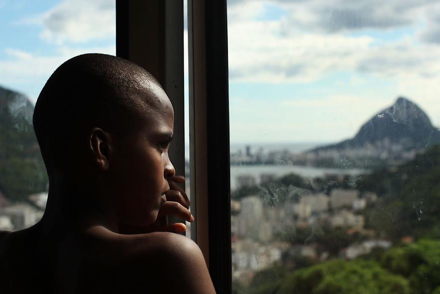 27. 13-летний Деванил Андраде де Суза младший смотрит Рио-де-Жанейро Санта Марта 3 декабря 2009 года. Деванил живет в бедном районе фавел с неработающей матерью и сестрой и хочет стать пожарным, когда вырастет. (Photo by Spencer Platt/Getty Images)