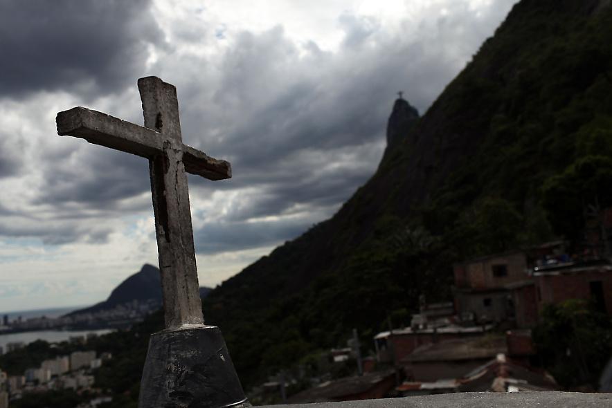 28. Церковный крест возвышается над недавно «зачищенным» районом фавел Санта Марта 3 декабря 2009 года в Рио. (Photo by Spencer Platt/Getty Images)