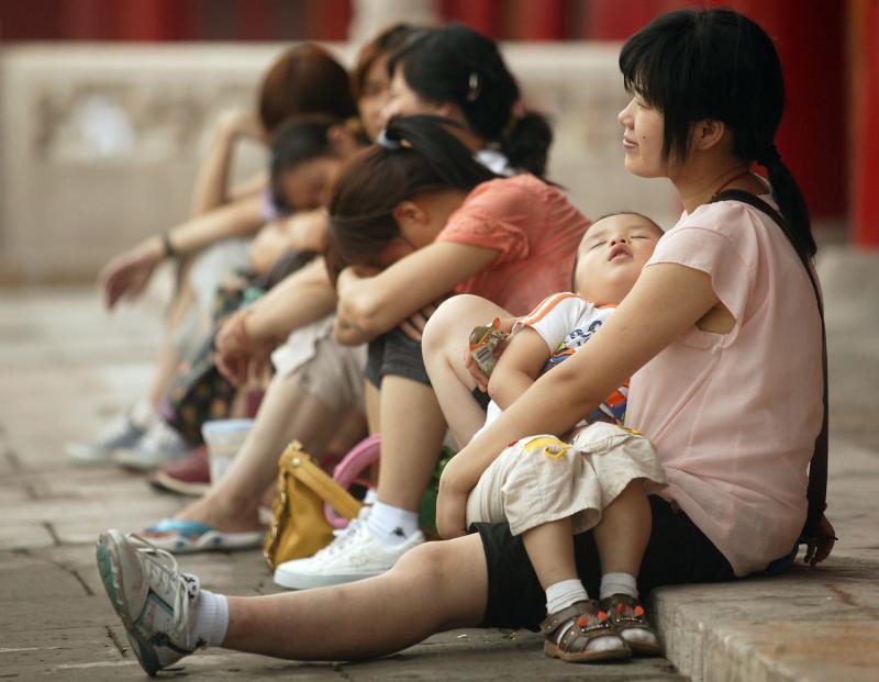 26) Китайские туристы отдыхают во время посещения Запретного города в преддверии Пекинских Олимпийских игр 2008 21 июля. (UPI Photo/Stephen Shaver)
