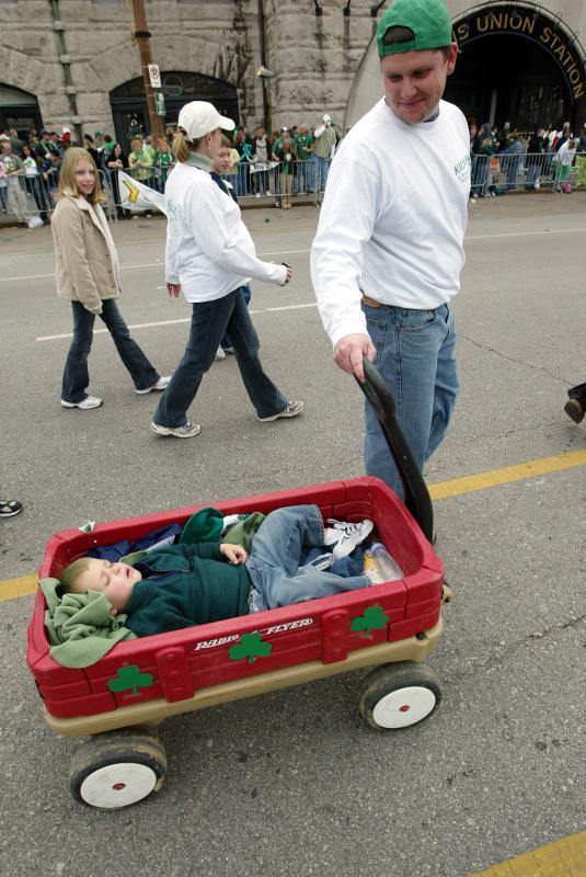 27) Джефф Годдард смотрит на своего спящего двухлетнего сына Дэнни во время парада в День святого Патрика в Сент-Луисе 12 марта 2005 года. (UPI Photo/Bill Greenblatt)