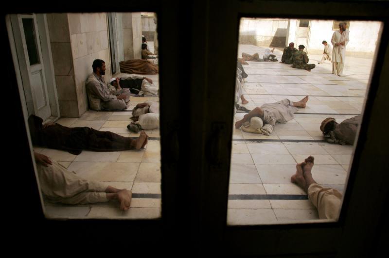 29) Люди видны в окно во время отдыха в мечети в Кабуле 15 сентября 2009 года. (UPI/Mohammad Kheirkhah)