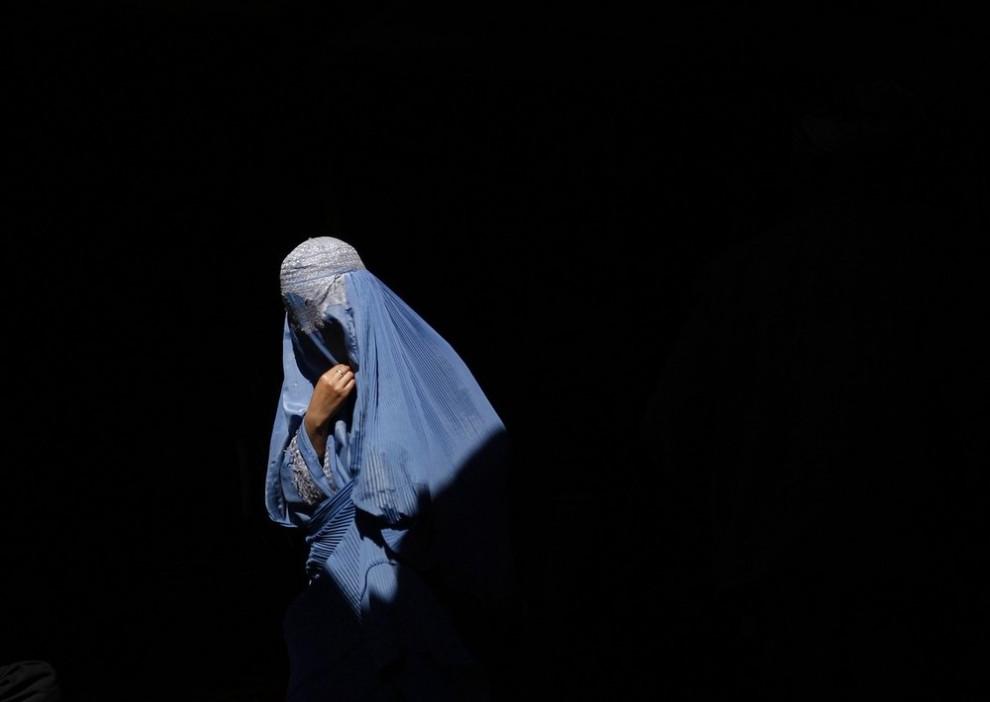 4) Афганская женщина в парандже идет на старом базаре в Кабуле 4 марта 2009 года. Избирательная комиссия заявила, что президентские выборы не могут быть проведены  в следующем месяце, как того требовал президент Хамид Карзай. Выборы, как и было запланировано ранее, пройдут 20 августа. (REUTERS/Ahmad Masood)