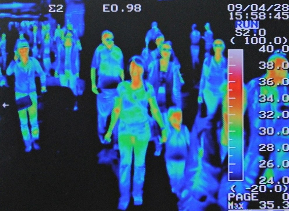 7) Тепловизионный сканер показывает признаки температуры у пассажиров международного рейса, прибывших в аэропорт Инчеон к западу от Сеула, 28 апреля 2009 года. В марте авиалинии столкнулись со спадом количества пассажиров по сравнению с прошлым годом, а вирус свиного гриппа только усугубил финансовую ситуацию. (REUTERS/Jung Yeon-je)