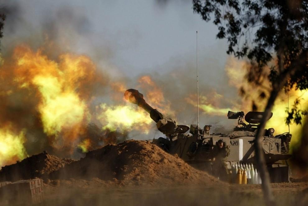 11) Израильский солдат закрывает уши во время выстрела из танка мобильной артиллерии в сторону Газа с пункта в центральной части Сектора Газа 6 января 2009 года. Во вторник Израиль ввел свои войска в южный город Газа. В 11-дневном конфликте погибли сотни палестинцев. (REUTERS/Baz Ratner)