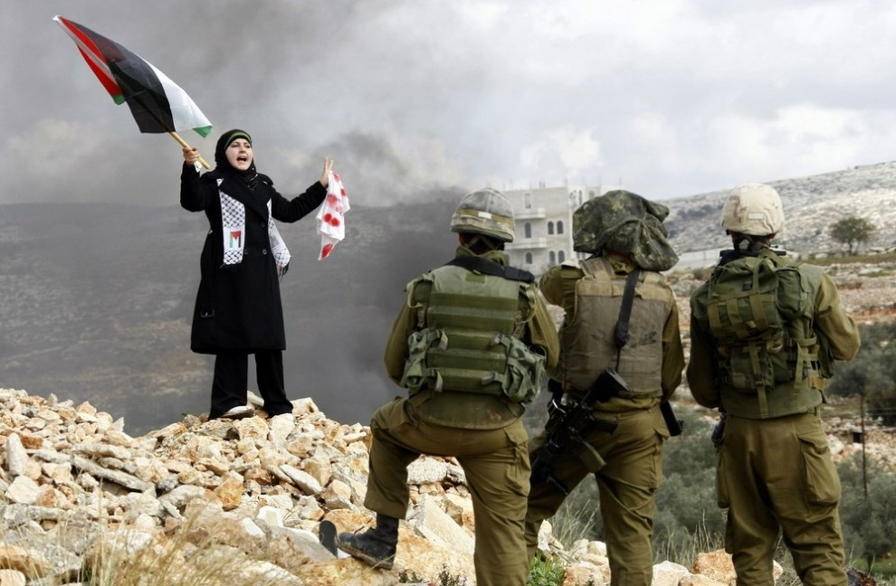 12) Палестинка стоит перед израильскими солдатами во время акции протеста в поселке Билин недалеко от города Рамалла. Протест был направлен против израильских боевых действий в городе Газа 8 января 2009 года. Несколько ракет, выпущенных из Ливана, ударили по северному Израилю в четверг, ранив двух человек. Эту атаку привязывают к войне с Израилем против исламистов группировки «Hamas» в Секторе Газа. (REUTERS/Eric Gaillard)