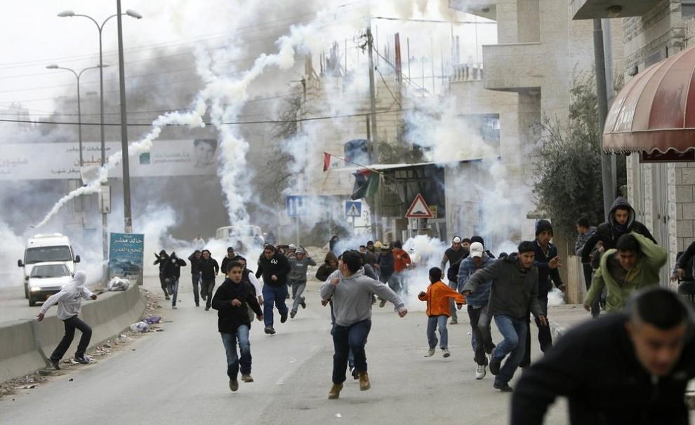 13) Демонстранты бегут от слезоточивого газа, который применила против них израильская пограничная полиция во время беспорядков на контрольном пункте Каландия недалеко от города Рамалла 16 января 2009 года. Опасаясь, что кризис в Секторе Газа повлечет за собой беспорядки и насилие на Западном берегу реки Иордан и в Восточном Иерусалиме, Израиль усилил контроль и внедрил в Старый город Иерусалима вооруженные войска на время еженедельных мусульманских молитв. (REUTERS/Fadi Arouri)