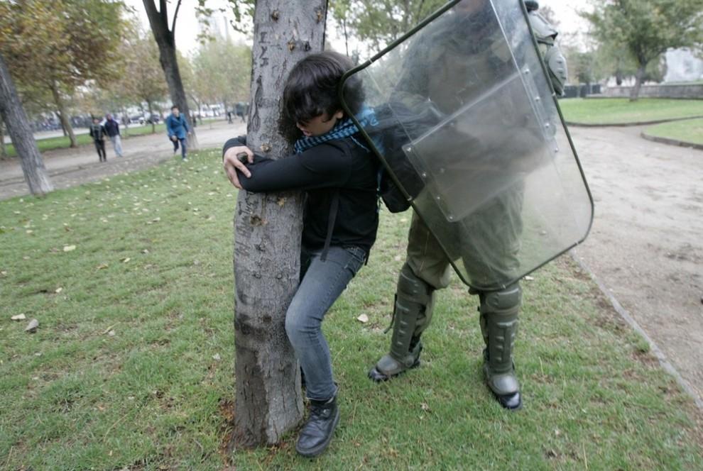 16) Полицейский из штурмового отряда пытается арестовать студента после акции протеста в Сантьяго 13 мая 2009 года. В среду студенты выступили за изменения в системе общественного образования и потребовали увеличения бюджета для университетов. (REUTERS/Victor Ruiz Caballero)
