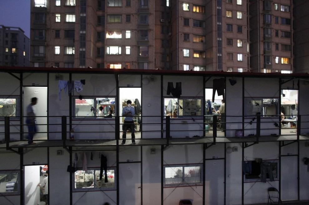 18) Строитель-мигрант проверяет свой мобильный телефон у общежития после рабочей смены на стройплощадке павильона выставки «Shanghai World Expo 2010» в Шанхае 15 апреля 2009 года. Уровень ВВП в Китае снизился до рекордно низкой отметки в первом квартале этого года, однако поквартальное увеличение может указывать на некоторые улучшения в экономике. (REUTERS/ Nir Elias)