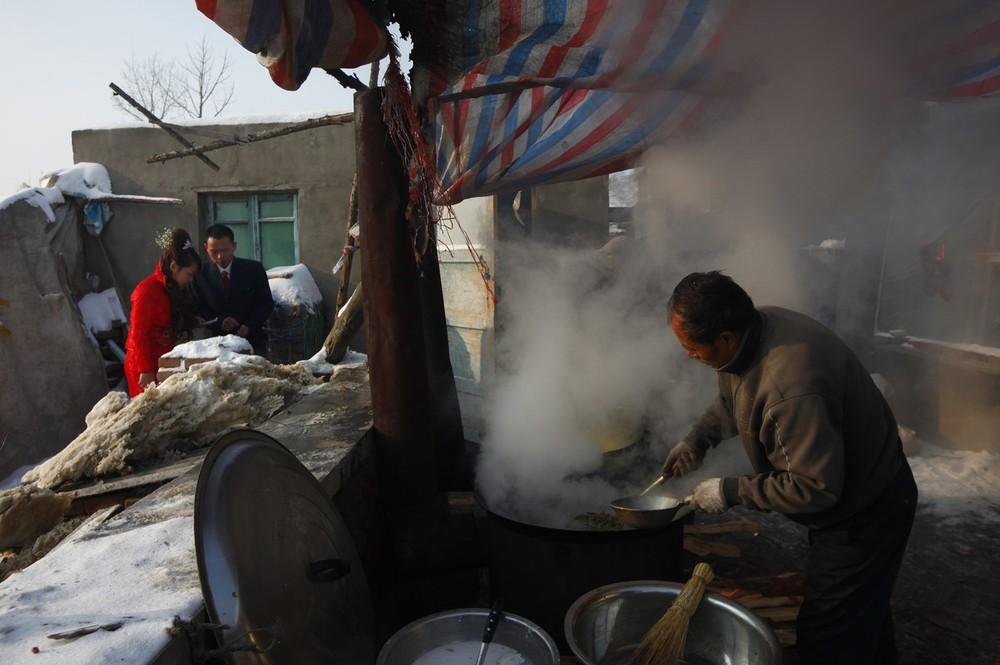 2) Повар готовит для свадебного обеда. По случаю свадьбы родители жениха должня заколоть свинью, установить временные кухонные плиты и позвать поваров. (Photo by China Photos/Getty Images)