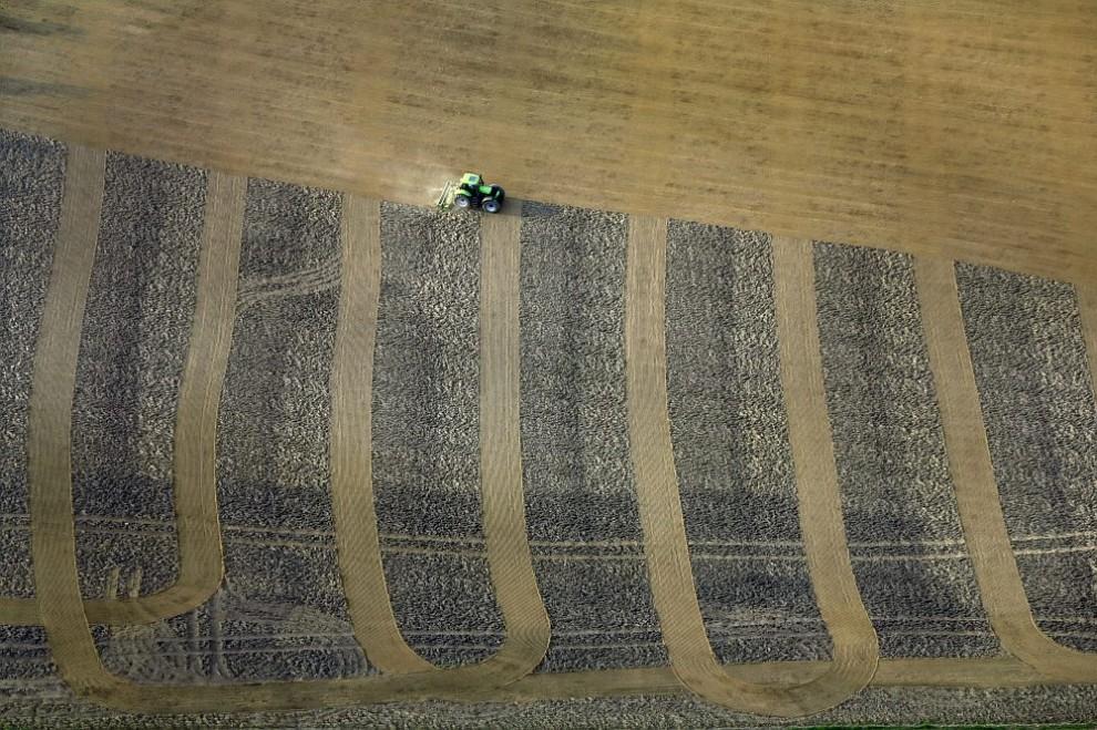 7. Вид с воздуха на трактор, собирающий в поле семена для возделывания кукурузы.