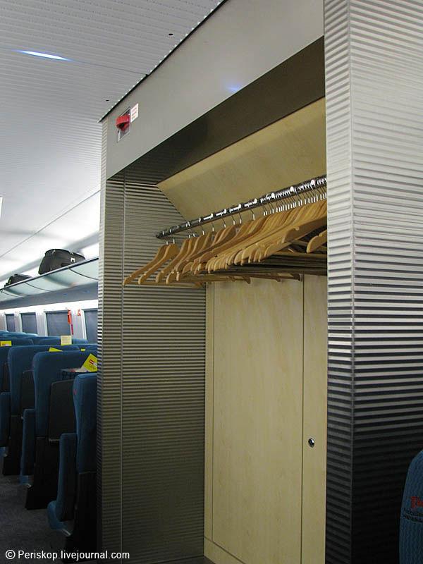 8) Раздеться можно двумя путями: в центре вагона есть гардероб с вешалками, хорошо видимый почти со всех рядов; а около окон есть вешалки, куда тоже можно повесить куртку. А вверху вы видите стоп-кран. Он ещё есть и в тамбурах. Багажные полки есть поверху рядов кресел, а также место в самом начале пассажирского салона, для массивных сумок с колёсиками.