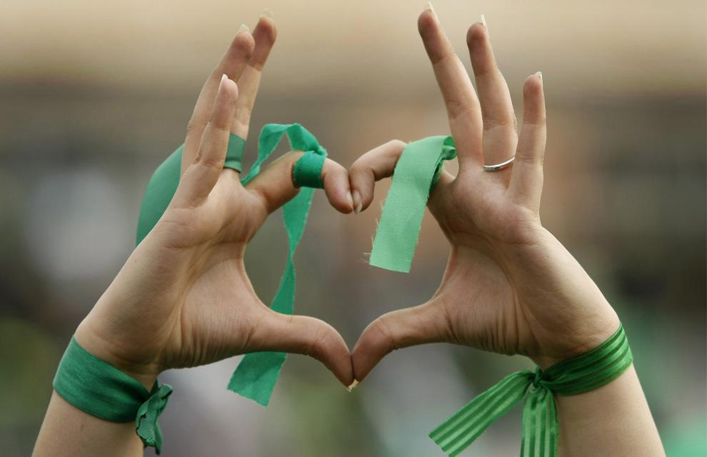 1. Сторонница кандидата-реформиста Мира Хосейна Мусави показывает сердечко руками, на которых повязаны зеленые ленточки - цвета партии. Снимок сделан на предвыборном митинге в Тегеране, во вторник, 9 июня 2009. (AP Photo/Ben Curtis)