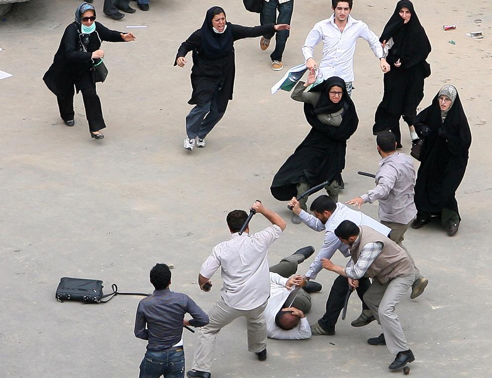 2. Добровольные военизированные полицейские и члены службы безопасности правительства страны избивают иранского сторонника проигравшего на президентских выборах кандидата Мира Хоссейна Мосави во время протестов в Тегеране 14 июня 2009 года. Молодые иранские противники президента Махмуда Ахмадинеджада вышли на улицы, поджигая мусорные баки и шины на второй день столкновений, спровоцированных слухами о фальсификациях на выборах. (AP Photo)
